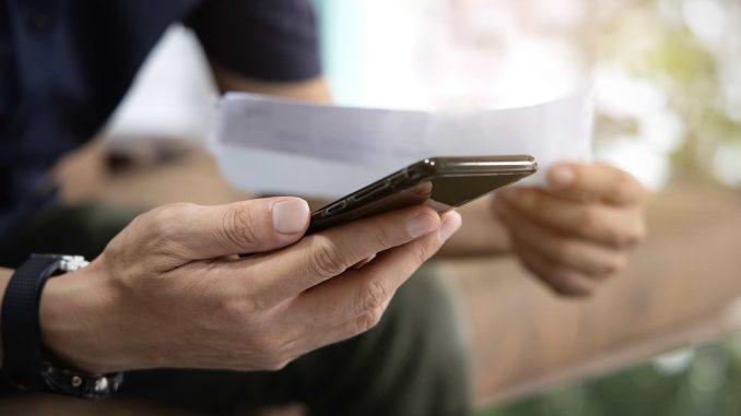 Man med mobil och faktura i händerna